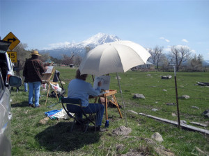 This photo is of a view of Mt. Shasta from Louis Road during Spring Workshop with an artist who is painting under a large white umbrella.